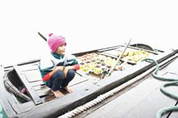 水上生活の中で果物を売り収入を得る子供